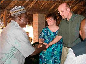 Dr. Thomas Asher, right, and Dr. Karen Asher, shown in Sierra Leone during an earlier trip, are co-founders of the Toledo-based West African Education and Medical Mission.