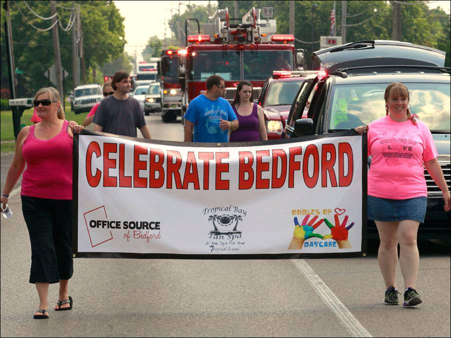Daisy Ritchie, left, and Kimberly Neyhart carry the Celebrate Bedford banner down Douglas Road.