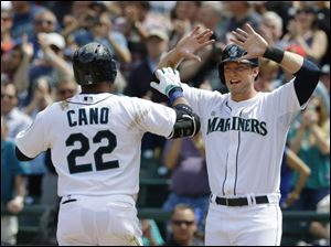 Seattle Mariners' Robinson Cano (22) is greeted by Mariners' Michael Saunders, right, after Cano hit a two-run home run that scored Saunders.