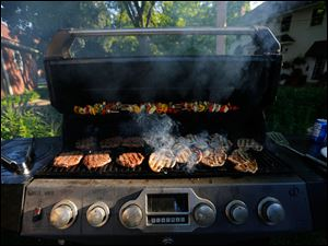 Burgers, pork chops and veggie kabobs fill the grill.