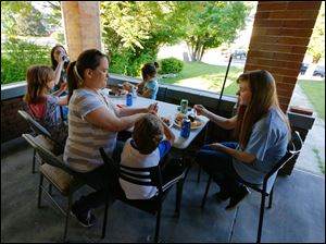 Jennifer Cload, Toledo, helps her son Jon, 4, with his food as daughters Savannah, 9, left, Kimberly, 16, Kasey, 7, and Mara, 13, enjoy the food from the porch.