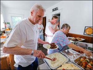 Bob Humanski, Toledo, and Kim Dresel, Toledo, fill their plates in the generous buffet.