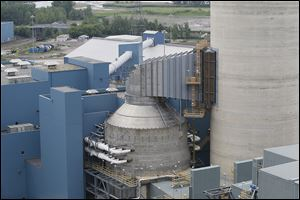 At right, the concrete building which connects to the stack houses the '‍scrubbers,' which use limestone to clean the exhaust Combined with a catalytic reduction system the process also removes mercury from the plant's emissions. A byproduct of the process is gypsum, which is the main ingredient in sheetrock.