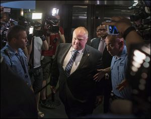Toronto Mayor Rob Ford, center, is greeted by a media throng as returns to his office at city hall today in Toronto.