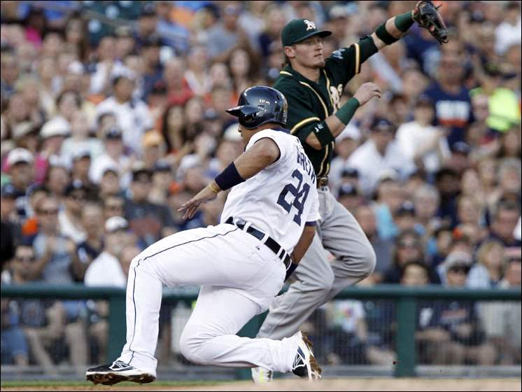 Detroit Tigers' Miguel Cabrera (24) slides in at third base past Oakland Athletics' Josh Donaldson on a double by Detroit Tigers' J.D. Martinez.