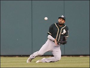 Oakland Athletics center fielder Coco Crisp makes a sliding catch of a fly ball hit by Detroit Tigers' Miguel Cabrera.