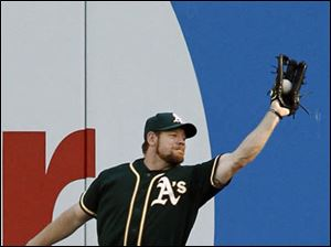 Oakland Athletics right fielder Brandon Moss reaches out to catch a fly ball hit by Detroit Tigers' Austin Jackson.