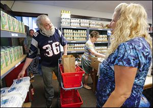 Jim Harder of Toledo shops under the guidance of Sue Shrewsbery of Catholic Charities' Helping Hands of St. Louis. The storelike model, unveiled Tuesday, was set up with help from the Toledo-Lucas County Health Department, Ms. Shrewsbery said.