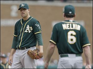 Oakland Athletics relief pitcher Jim Johnson stands on the mound as manager Bob Melvin walks up during the sixth inning.