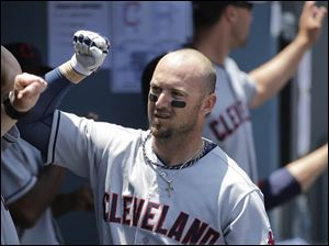 Cleveland Indians' Ryan Raburn celebrates his two-run home run in the dugout.
