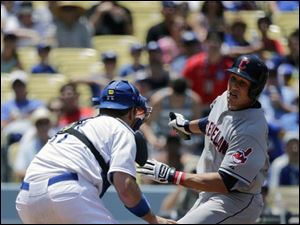 Los Angeles Dodgers catcher A.J. Ellis, left, applies a tag to Cleveland Indians' Asdrubal Cabrera as Cabrera tries to score on a single hit by Carlos Santana.