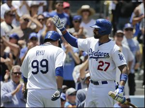 Los Angeles Dodgers starting pitcher Hyun-Jin Ryu, left, of South Korea, is greeted by teammate Matt Kemp after scoring on a single hit by Andre Ethier.