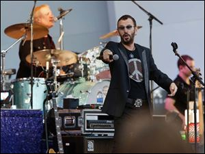 Former Beatle Ringo Starr holds his microphone to the crowd.