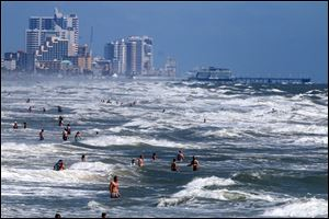 People deal with the high surf and currents off Daytona Beach generated by Tropical Storm Arthur on Tuesday.