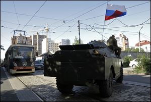 A pro-Russian fighters' APC travels near the captured Interior Ministry