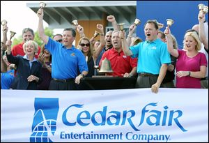 Cedar Fair CEO Matt Ouimet, center, rings the closing bell on the daily session of the New York Stock Exchange Wednesday, at Cedar Point in Sandusky, Ohio. To his left are CFO Brian Witherow and Shannon Rochford of the NYSE. At Mr. Ouimet's right is COO Richard Zimmerman and VP Stacy Frole.