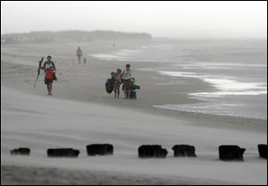 Clouds and rains move in as beachgoers leave Freeman Park at the north end of Carolina Beach, N.C., today.