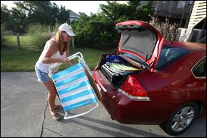 Carol Palmer of King George, Va.  loads a car with her family's belongings as they prepare to leave Hatteras Village, N.C.