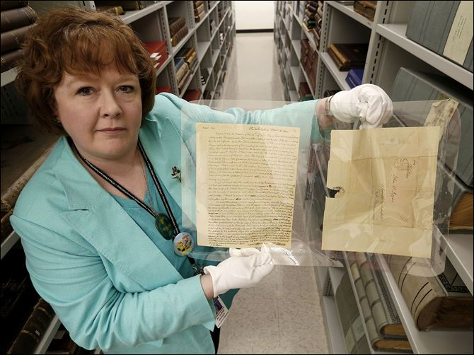 n6jeffersonletter-1 Jill Clever, manager of the Local History and Genealogy Department at the Toledo-Lucas County Public Library, holds an original letter and envelope written by Thomas Jefferson.