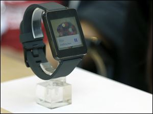 A woman looks at the LG G Watch, an Android Wear smart watch, on the demo floor at Google in San Francisco. The smart watch, which will be available soon, still is somewhat limited in what it can do, and even last year's smart watches do some things that Android Wear software can't.