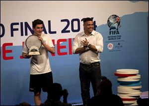 Denmark's August Rosenmeier, left, winner of the FIFA Interactive World Cup 2014, holds a trophy while Brazil's former soccer great Ronaldo applauds, during the FIFA Interactive World Cup 2014 Grand Final at Sugar Loaf, Rio de Janeiro, Brazil.