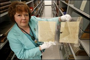 Jill Clever, manager of the Local History and Genealogy Department at the Toledo-Lucas County Public Library, holds an original letter and envelope written by Thomas Jefferson.