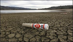 A warning buoy sits on the dry, cracked bed of Lake Mendocino near Ukiah, Calif. Com­pe­ti­tion for wa­ter in Cal­i­for­nia is height­ened by the state's ge­og­ra­phy: The north has the wa­ter re­sources, but the big­gest wa­ter con­sum­ers are to the south.