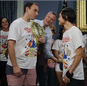 New York City Mayor Bill de Blasio watches Joey Chestnut, left, and Matt Stonie, right, during a news conference to promote the upcoming Nathan's Famous Fourth of July Hot-Dog Eating Contest at City Hall in New York.