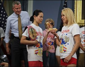 New York City Mayor Bill de Blasio watches hot dog eating contestants Sonya Thomas, left and Miki Sudo, right during a news conference Thursday. Defending champion Thomas lost to Sudo today.