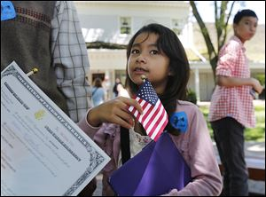 '‍Freedom, freedom, freedom,' Sarah Xaiyarath, 7, of Northwood, answered for her mother, Martha Vieng Xaiyarath, about why she became a U.S. citizen. Mrs. Xaiyarath was one of 46 people from 29 countries to take the oath at Sauder Village in Archbold, Ohio.