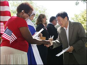 Johnny Taylor, left, of the League of Women Voters, gives new citizen Yan Namsrai, formerly of Mongolia, information on voting. U.S. District Judge James R. Knepp II presided over the ceremony on Friday.
