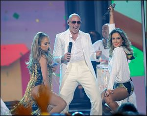 Some artists such as Pitbull, center, use as many as eight writers to create a song.
