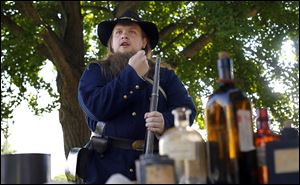 Civil War re-enactor Tyler Bury gives a presentation about loading a musket during the Whitehouse celebration. The village was founded in 1864.