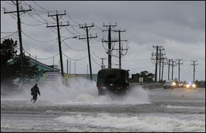 A military vehicle and a man navigate a flooded Highway 64 as wind pushes water over the road while Hurricane Arthur passes through Nags Head, N.C.