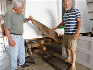 Brooke Brown, left, and Bill Moon hold a rotted piece of a beam. They replaced about 3 feet of the rotted beam that was on the base of the lighthouse.