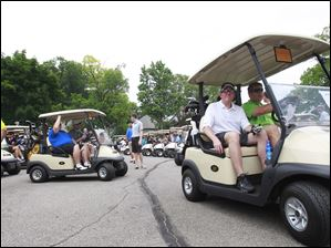 Golfers drive to their first holes to tee off to begin the 2014 Savage Foundation Golf Classic held at the Stone Oak Country Club in Holland, Ohio.