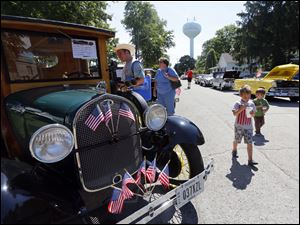 Jeremy Head, left, and Dawn Head, right, from Maumee, look at historical cars including this 1929 Ford Huckster.