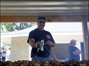 Whitehouse Volunteer Firefighter Neil Raymond, tends to the BBQ chicken.