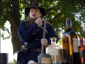 Re-enactor Tyler Bury gives a presentation about loading a musket.