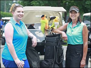 Lindsay Bowerman, left, and Lisa Heinrich, right, stand for a picture with their golf clubs during the 2014 Savage Foundation Golf Classic held at the Stone Oak Country Club in Holland, Ohio.