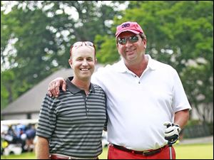 Mark Smigelski, left, one of the owners of Savage and Associates, and Dave Fockler, right, stand for a picture on the putting green during the 2014 Savage Foundation Golf Classic held at the Stone Oak Country Club in Holland, Ohio.