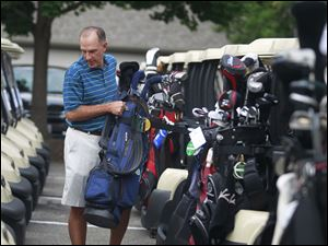 Todd Schultz loads his golf clubs onto his golf cart during the 2014 Savage Foundation Golf Classic held at the Stone Oak Country Club in Holland, Ohio.