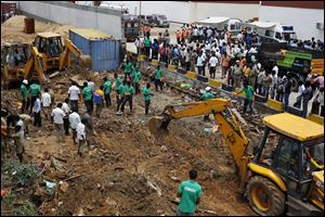 Workers clear the debris after the boundary wall of a warehouse collapsed today on the outskirts of Chennai, India.