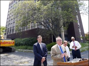 Mayor D. Michael Collins, center, speaks in front of the former Clarion Hotel which will be demolished. Toledo City Councilman Matt Cherry, left, Block watch president David Lemon, and Toledo City Councilman Larry Sykes, right, stand nearby.