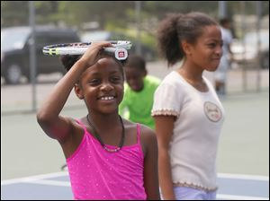 Tatiyana Esmond, 8, balances her racquet on her head.
