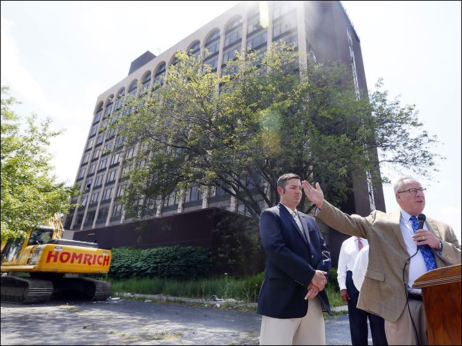 n3clarion Mayor D. Michael Collins, in front of the former Clarion Hotel, calls the start of its razing an important step to remove blight. Councilman Matt Cherry, left, stands nearby. The hotel has stood empty since 2009 and has since caught fire and been vandalized.