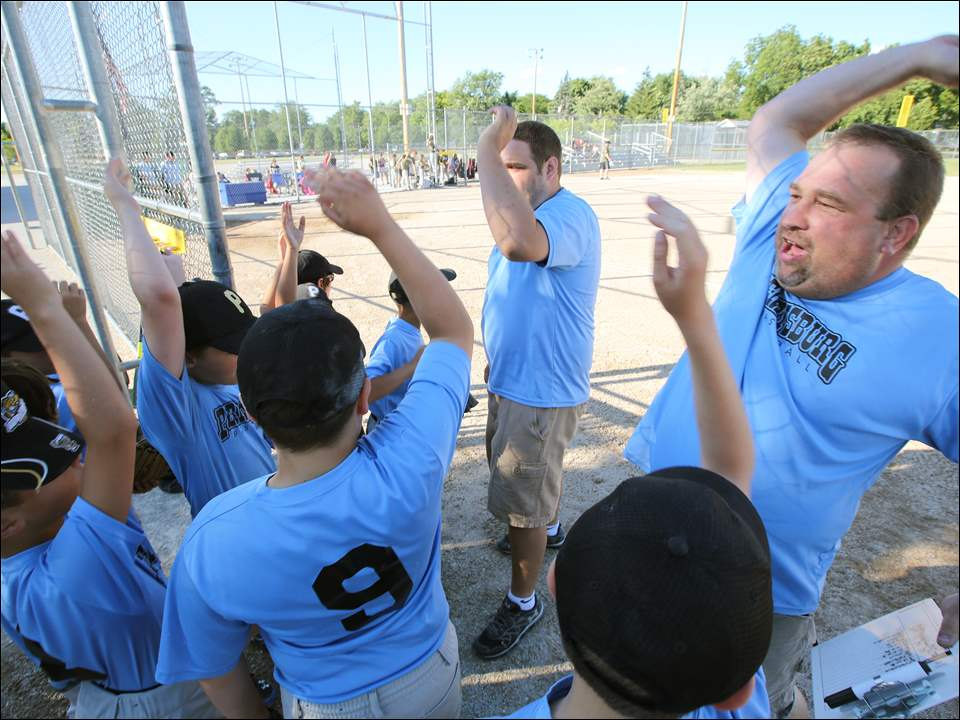 Jim Schwamberger, coach of the Light Blue team, leads his team in a cheer between innings during a league playoff game against the Army Green team at Municipal Park in Perrysburg.