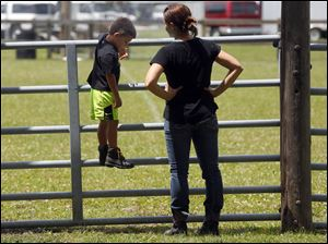 Cash Carroll, 4, left, and his mother Jen Carroll, right, from Whitehouse stand on the fence to the horse ring while Cash's grandmother Jeanne Carroll's pony practices.