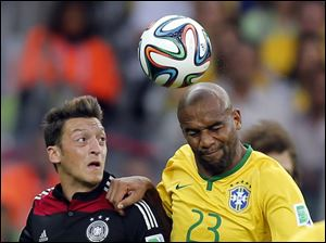 Germany's Mesut Ozil, left, and Brazil's Maicon go for a header.