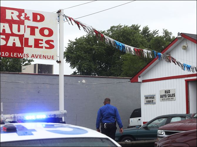 CTY R&D Shooting08p Law enforcement officials investigate the scene of a shooting and possible robbery  at R&D Auto S